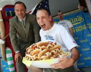 NEW YORK - JULY 03:  World record holder Joey Chestnut poses at the Nathan's Famous Fourth of July International Hot Dog Eating Contest official weigh-in ceremony while holding 59 1/2 hot dogs July 3, 2007 in New York City. Chestnut defeated former record holder and arch rival Takeru Kobayashi of Japan by downing 59 1/2 hot dogs at a recent contest in Tempe, Arizona.  (Photo by Mario Tama/Getty Images)