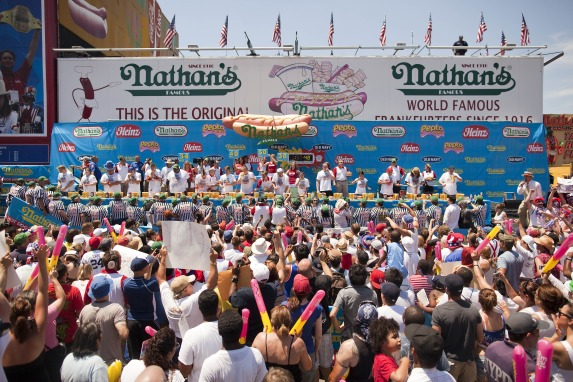 NEW YORK - JULY 4:  Competitive eaters participate in the 2010 Nathan's Famous Fourth of July International Hot Dog Eating Contest at the original Nathan's Famous in Coney Island on July 4, 2010 in the Brooklyn borough of New York City.   Chestnut won this year's International Federation of Competitive Eating event, eating 54 hot dogs, while his biggest rival Takeru Kobayashi didn't compete due to a contract dispute with Major League Eating. Subsequently, Kobayashi was arrested for attempting to hop a barricade and get on the stage after the event, charges are pending. (Photo by Michael Nagle/Getty Images)